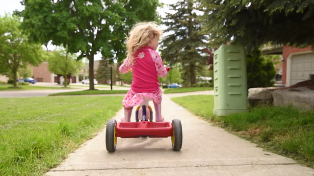 young girl riding her tricycle. - tricycle stock videos & royalty-free footage