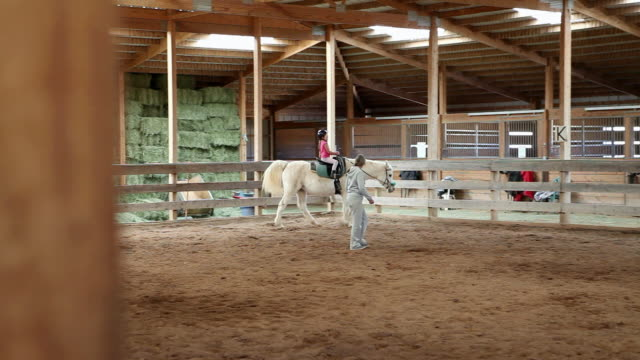 MS PAN Young girl riding horse with her instructor / Lamy, New Mexico, United States