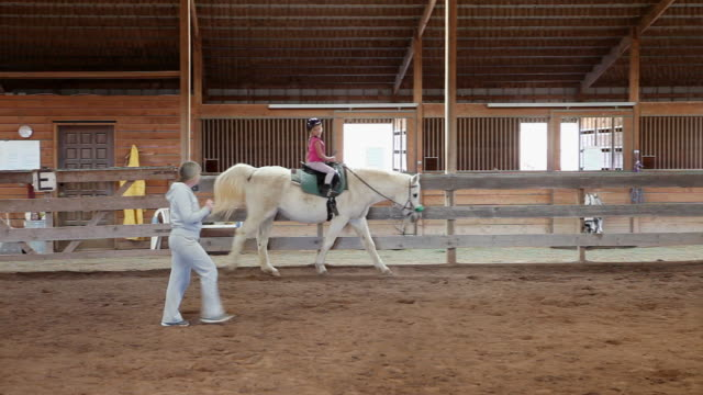 ms pan young girl riding horse with her instructor / lamy, new mexico, united states - lamy new mexico stock videos and b-roll footage