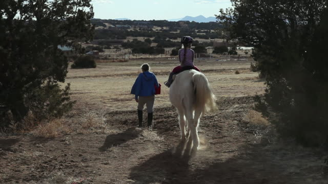 ms young girl riding horse with her instructor / lamy, new mexico, united states - lamy new mexico stock videos & royalty-free footage