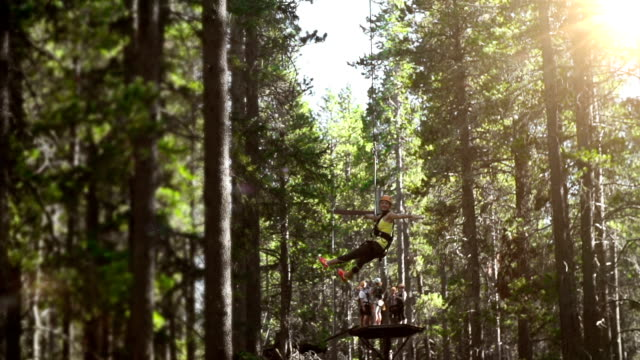 young girl riding zip line in forest - zip line stock videos & royalty-free footage