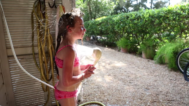 MS TU TD Young girl rinsing herself off in outdoor shower / St. Simon's Island, Georgia, United States