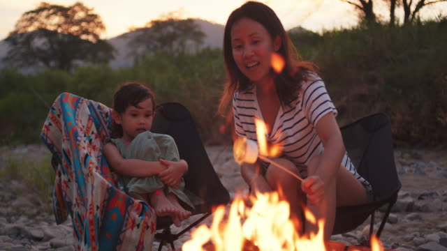 キャンプファイヤーで母親とマシュマロを焙煎する若い女の子 - キャンプする点の映像素材/bロール