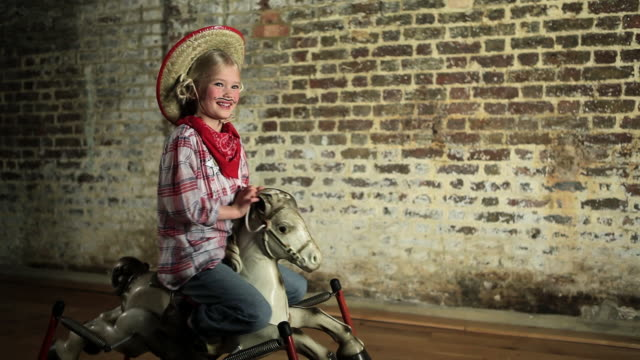 Young girl rocking on rocking horse