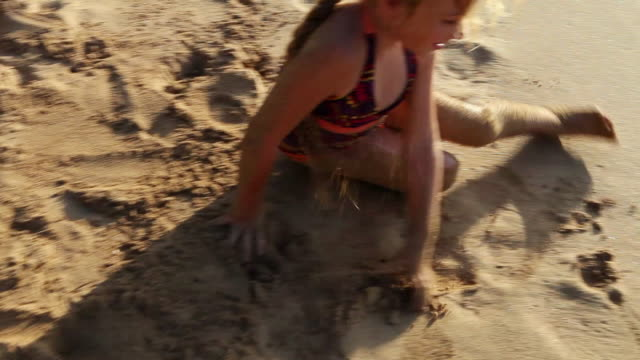 vídeos de stock e filmes b-roll de ms ts young girl rolling in sand on beach / kauai, hawaii, united states - rolar