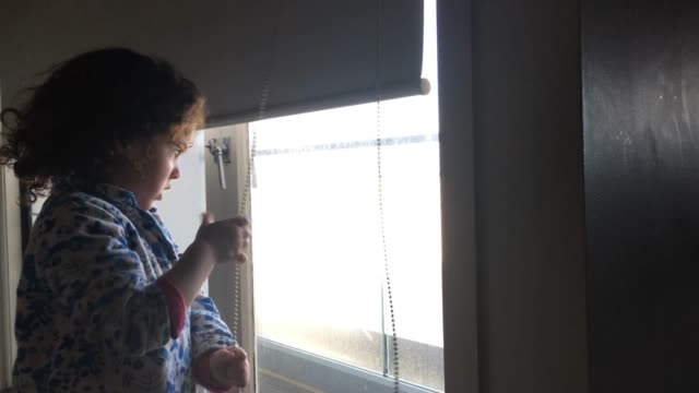 young girl rolling up window curtain in the morning - tapparella video stock e b–roll