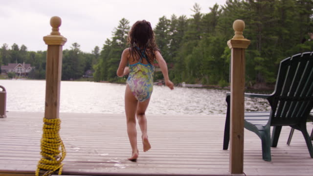 young girl running and jumping off dock into lake - only girls stock videos & royalty-free footage