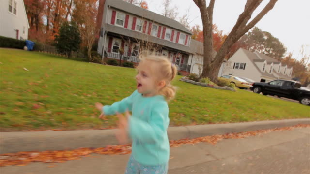 Young girl running down a street happily in suburbia, USA reaches out and touches camera