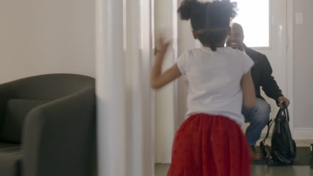 young girl running down hallway to greet father. - young family stock videos & royalty-free footage