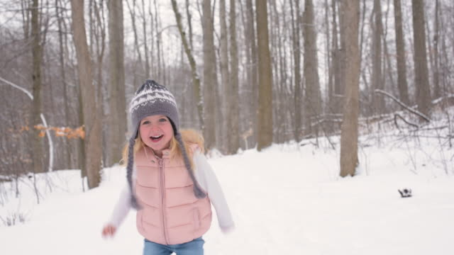 vídeos de stock, filmes e b-roll de young girl running down snow covered trail - roupa quente