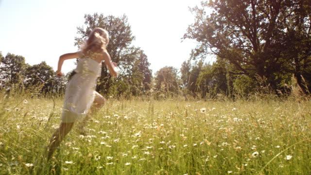 SLO MO menina a correr para a relva em dia de sol