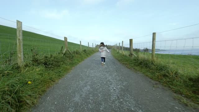 曇天の冬の田舎で走っている若い女の子 - 幼児点の映像素材/bロール