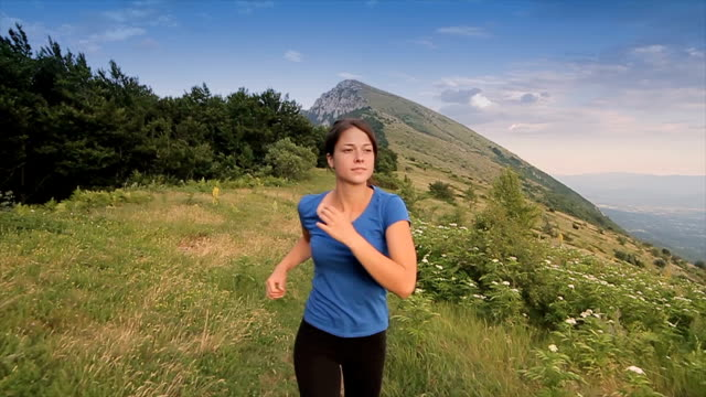 Young girl running on the top of the mountain,camera stabilization shoot