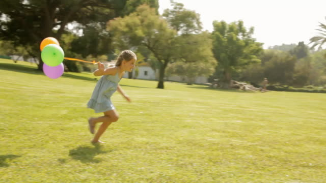 young girl running with balloons in park - side view stock videos & royalty-free footage