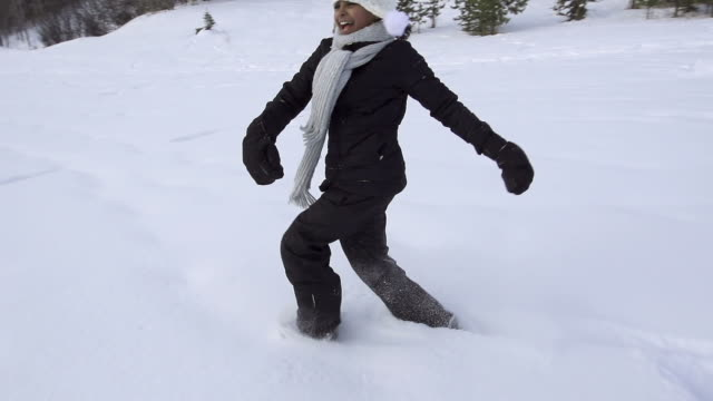 Young girl runs and creates snow angel