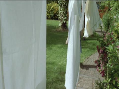 Young Girl Runs Down a Garden Path Through Sheets Hanging on a Washing Line