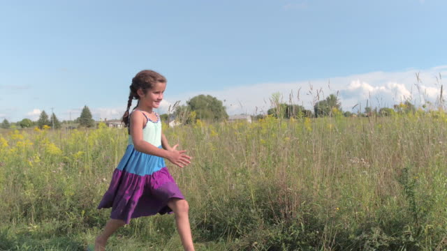 young girl runs in the grass - schoolgirl stock videos & royalty-free footage