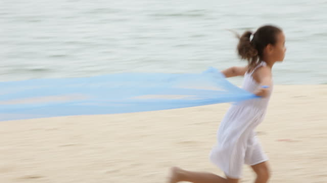 a young girl runs on a beach, holding a billowing blue scarf behind her. - 6 7 years stock videos & royalty-free footage