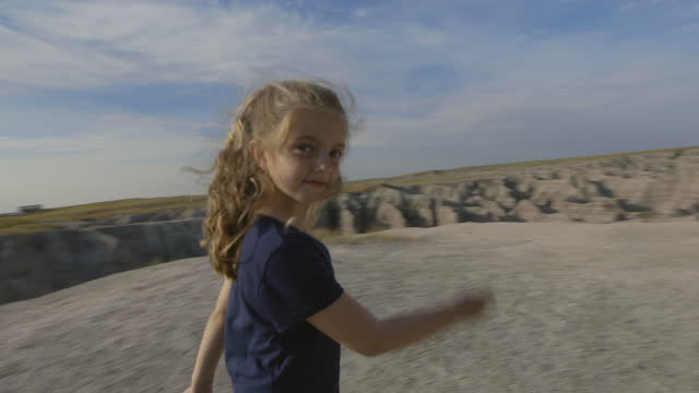 Young girl runs to catch up with brother and smiles at camera on family trip to Badlands National Park.