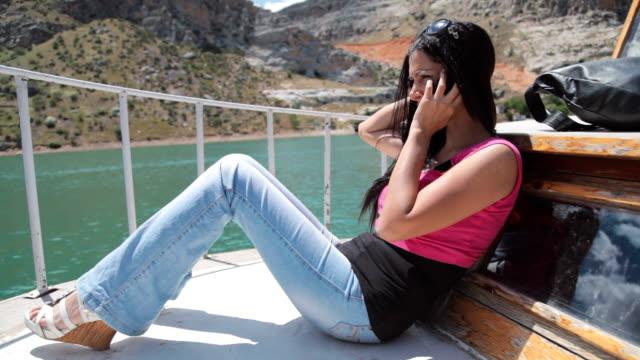 若い女の子のセーリングヨット電話で、