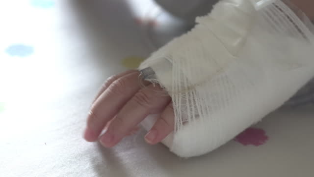 young girl saline solution on bed in rehabilitation room, saline solution drip on hand. - saline drip stock videos and b-roll footage