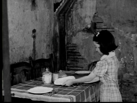1935 b/w ws young girl setting table / tilt up run down wall of house / slums / usa - great depression stock videos & royalty-free footage