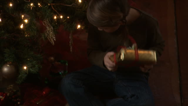 A young girl shaking Christmas presents