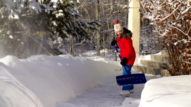 young girl shoveling snow on walkway - snow stock videos & royalty-free footage