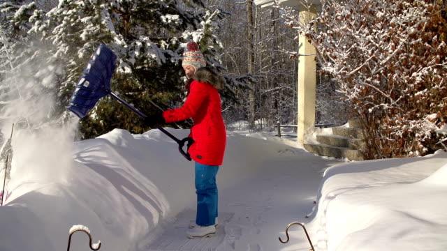 Junges Mädchen B. beim Schneeschaufeln auf Bürgersteig