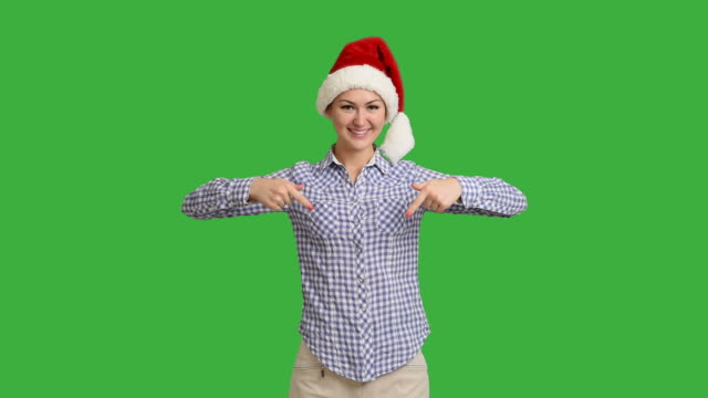 young girl shows copy space in shirt and santa hat on a green screen - red dress stock videos & royalty-free footage