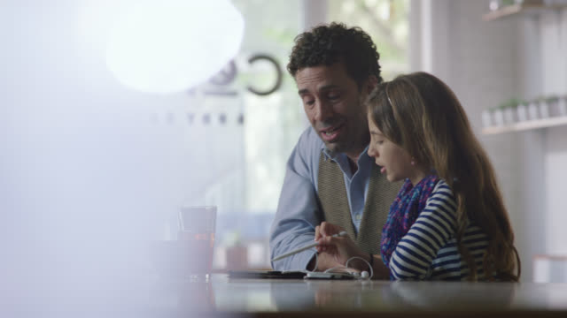 MS. Young girl shows father how to use tablet in modern coffee shop.