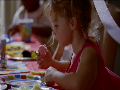 young girl sits at a table eating cake from a disposable plate at a birthday party - disposable stock videos and b-roll footage