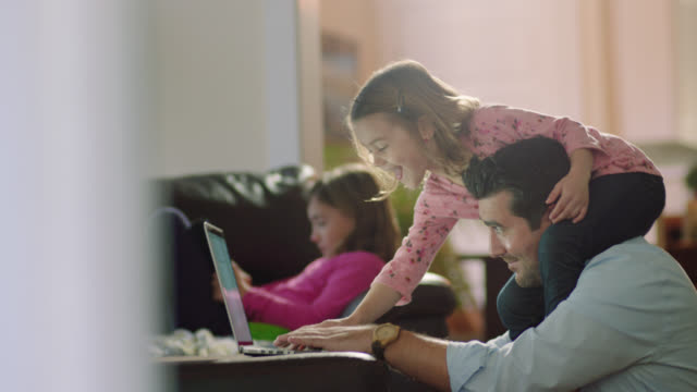 stockvideo's en b-roll-footage met ms. young girl sits on dad_s shoulders and leans down to type on his laptop while he attempts to work from home. - familie