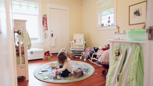 WS Young girl sitting in bedroom putting shoes on doll/Seattle, Washington, USA
