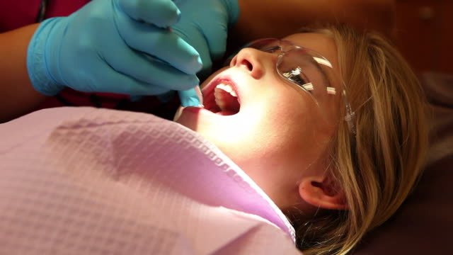 MS Young girl sitting in dentist chair / Lamy, New Mexico, United States