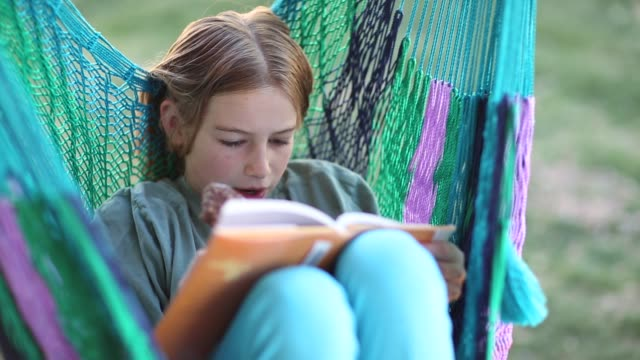 young girl sitting in hammock on porch - pre adolescent child stock videos and b-roll footage