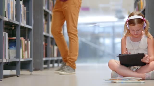 vídeos y material grabado en eventos de stock de ds joven sentado en la biblioteca pasillo navegando por comprimido - auriculares aparato de información