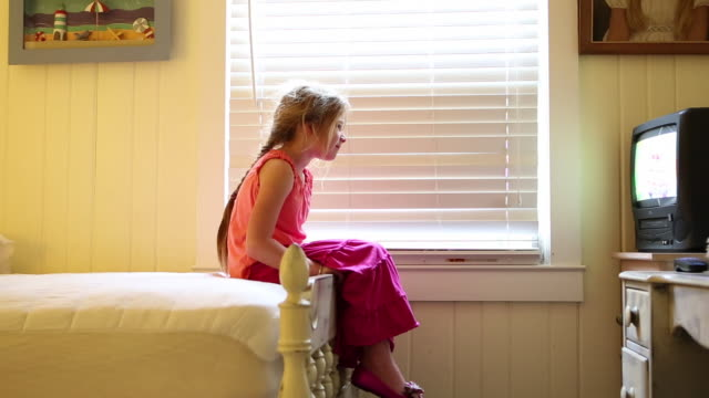 MS Young girl sitting on edge of her bed and watching television / St. Simon's Island, Georgia, United States