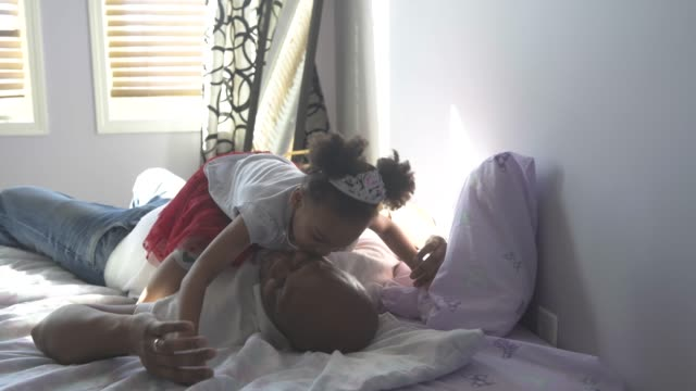 young girl sitting on her father's belly. - nightwear stock videos & royalty-free footage