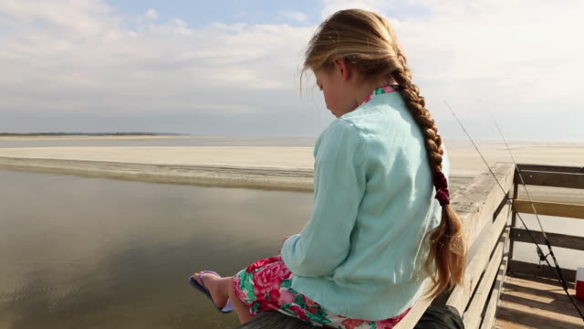 MS Young girl sitting on pier / St. Simon's Island, Georgia, United States