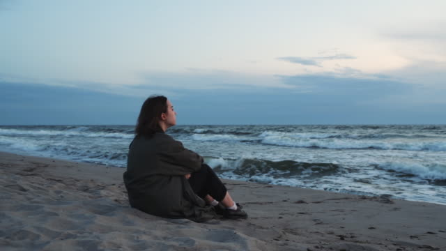 young girl sitting on the beach at sunset - serene people stock videos & royalty-free footage