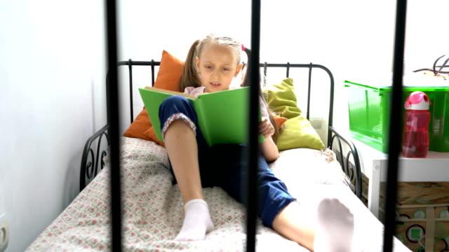 junges mädchen auf dem bett sitzt und ihr text-buch - 6 7 jahre stock-videos und b-roll-filmmaterial