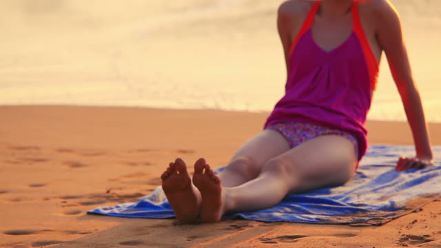 vídeos y material grabado en eventos de stock de chica joven sentada en la playa tropical - sólo una adolescente