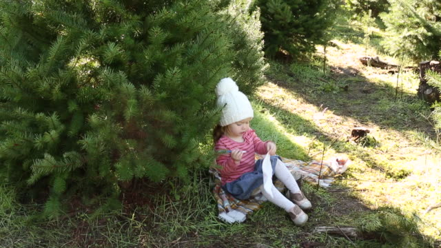 stockvideo's en b-roll-footage met a young girl sitting under a christmas tree outside on a farm. - panty
