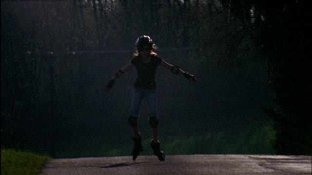 a young girl skates on a forest road. - sportschützer stock-videos und b-roll-filmmaterial