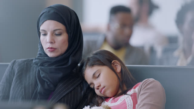 young girl sleeps on mother's shoulder in waiting area of airport terminal near gate. - mother's day stock videos & royalty-free footage