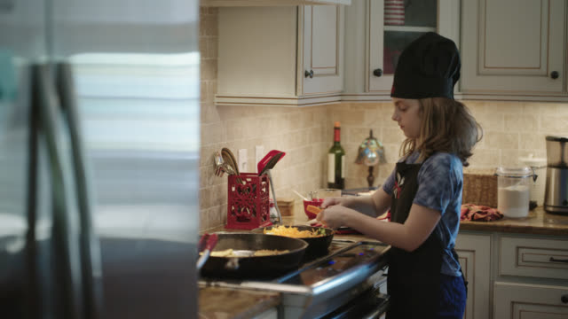 young girl slicing carrots into a cast iron skillet. - フライパン点の映像素材/bロール