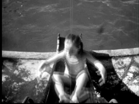 1945 HA MS Young girl sliding backward down water slide into swimming pool/ Sylacauga, Alabama