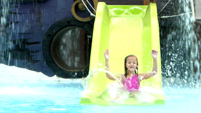 vidéos et rushes de jeune fille glisse toboggan aquatique - toboggan