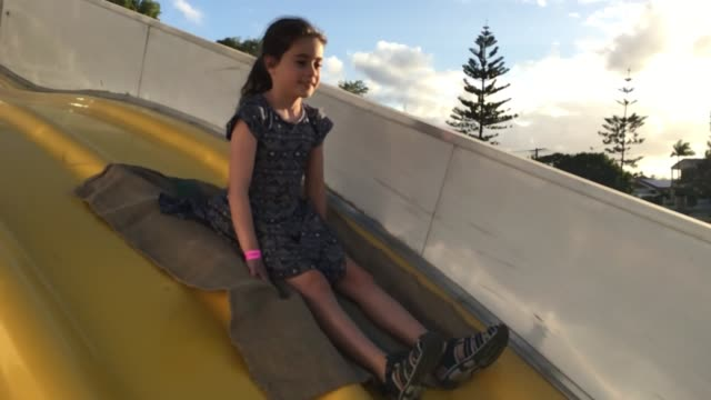 Young Girl Sliding on a Large Slide Outdoors